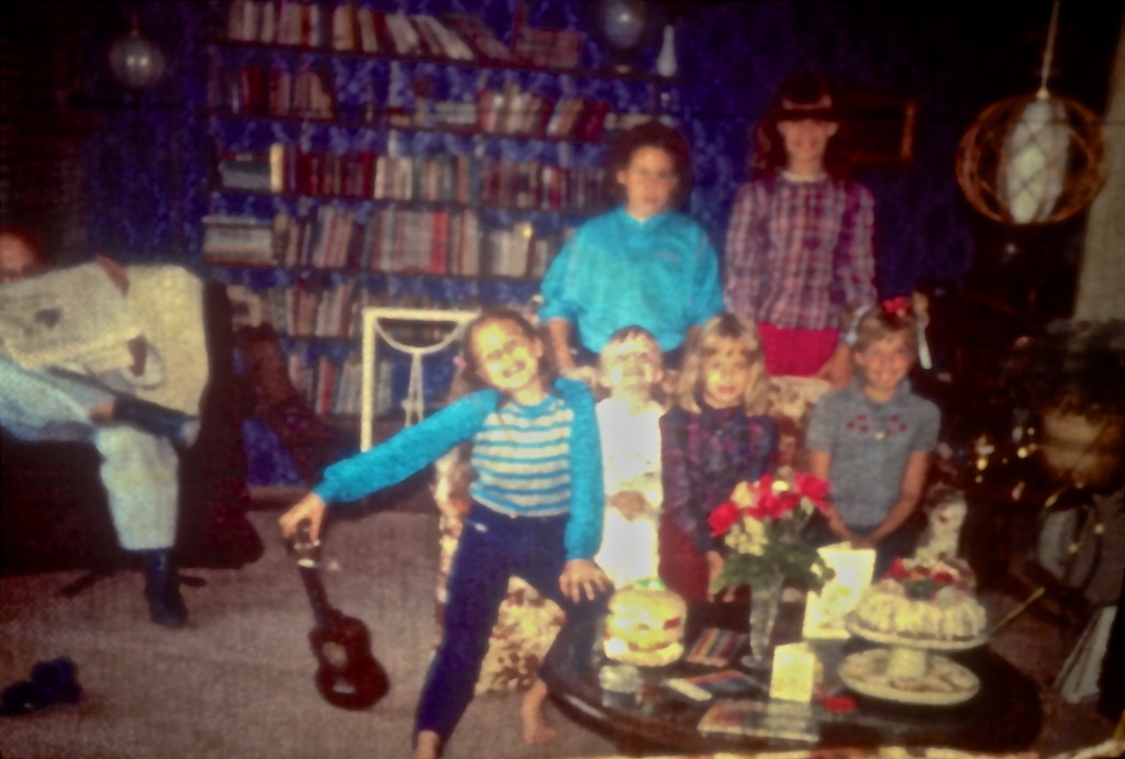 A picture taken moments before the end of the party. That's my sister with the ukelele, and I am on the right side with the red bow stuck to my head, You can see my mom's  chocolate bundt cake as well as the crystal bud vase with roses from the garden. It looks like my presents were markers and pencil crayons plus a very large hamburger coin bank, which I loved.  One other note: Michelle, the tall one in the back, is wearing red pants borrowed from my mother since her white ones got soaked with  balloon water.